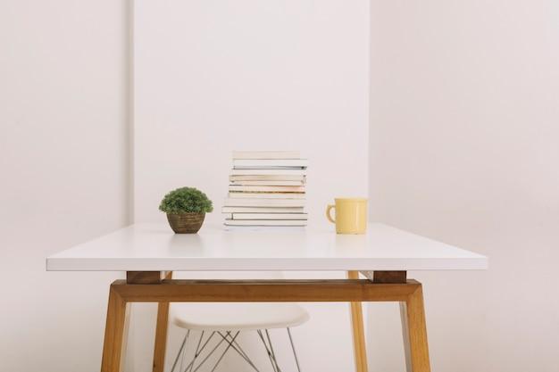 Plante et tasse près de livres sur table