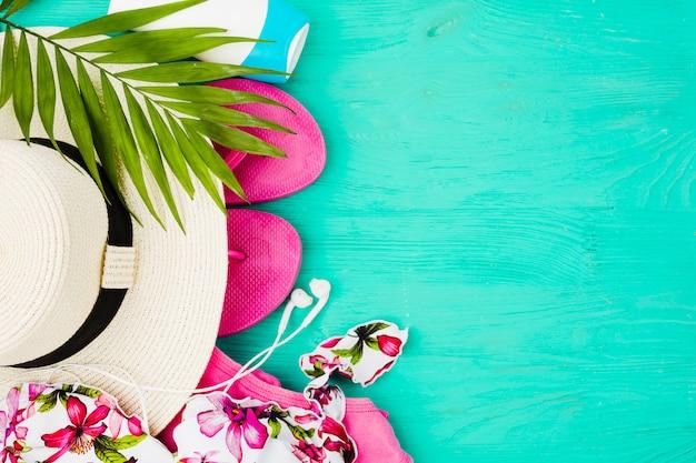 Planter le feuillage et le maillot de bain près des tongs et du chapeau