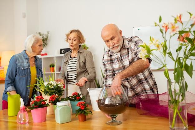 Planter des fleurs. bel homme âgé debout près du vase avec du sol tout en plantant des fleurs dedans