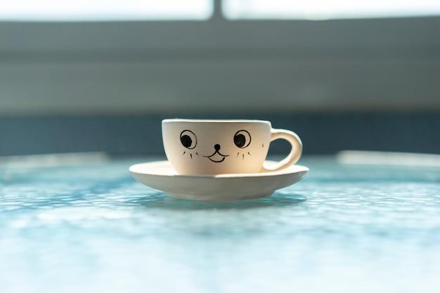 Planter des pots sous la forme de tasses à café avec joli visage souriant