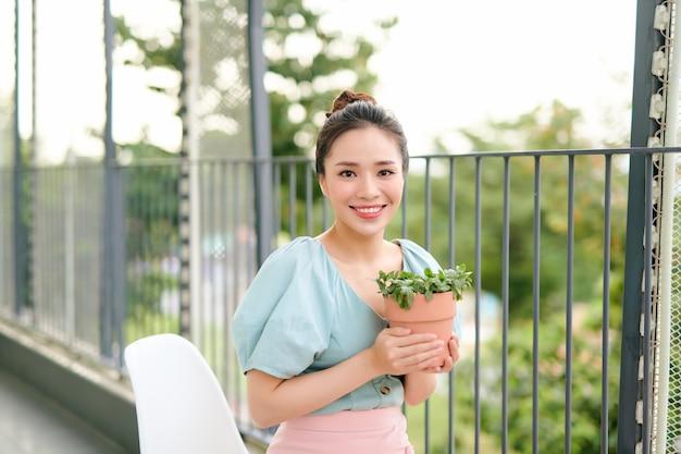 Plantes vertes en pot dans de belles mains de femme asiatique heureuse sur balcon