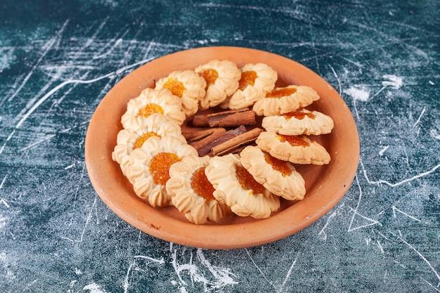 Plaque d'argile pleine de biscuits à la gelée et de bâtons de cannelle sur une surface en marbre.