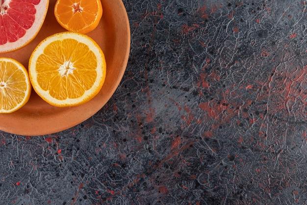 Plaque d'argile avec des tranches d'orange, de citron et de pamplemousse sur une surface en marbre