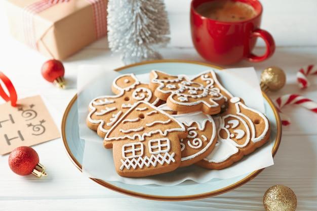 Plaque avec biscuits de noël, jouets, coffrets cadeaux et café sur bois blanc, gros plan