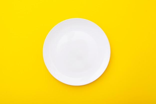 Plaque blanche en céramique sur surface jaune, table de cuisine, mise en page, vue de dessus, espace pour le texte