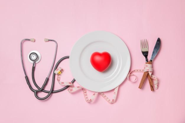 Plaque blanche coeur rouge et stéthoscope avec ruban à mesurer autour de fourchette et couteau isolé, concept de soins de santé et de régime