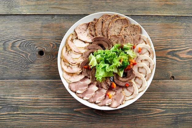 Plaque blanche sur une table en bois pleine d'assortiment de tranches de viande farcies