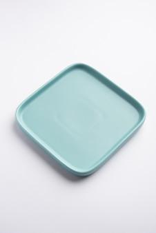 Plaque carrée en céramique vert clair ou bleu vide isolé sur fond blanc