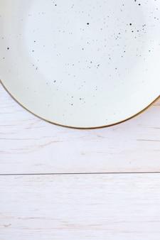 Plaque en céramique blanche sur la surface du bois, vue du dessus
