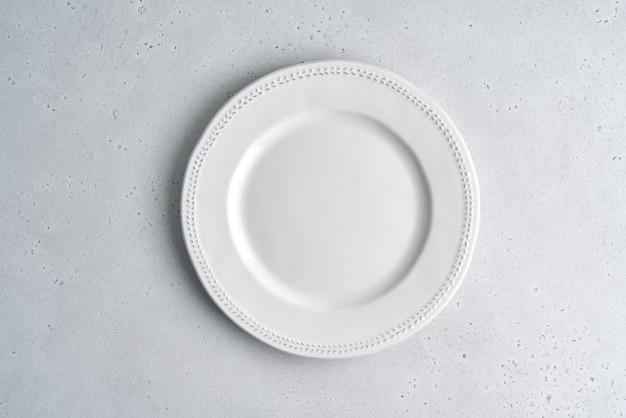 Plaque en céramique blanche vide sur fond clair copie espace vue de dessus gros plan horizontal