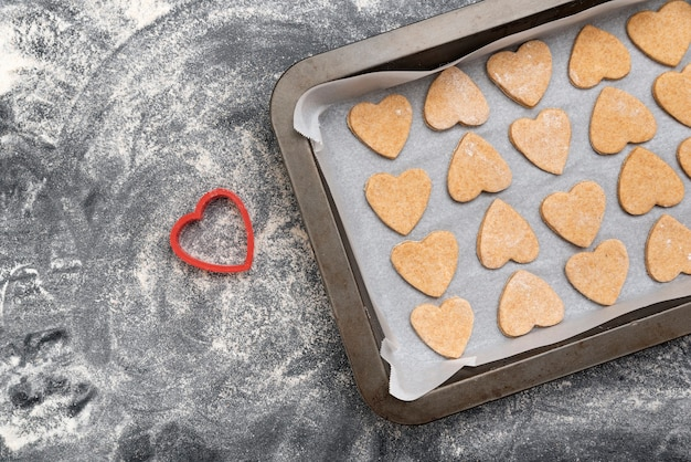 Plaque de cuisson avec des cookies en forme de cœur sur la table noire