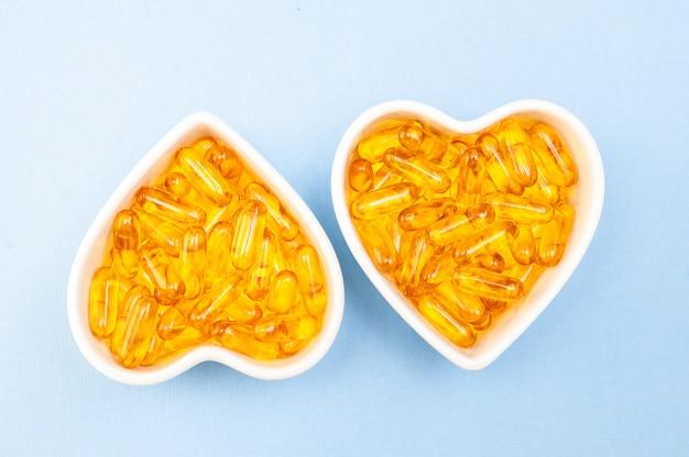 Plaque en forme de coeur avec des capsules d'huile de poisson oméga 3, produit sain et concept de supplément close up, mise à plat