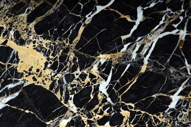 Une plaque de marbre noir coûteux avec des veines jaunes et blanches s'appelle new portoro.