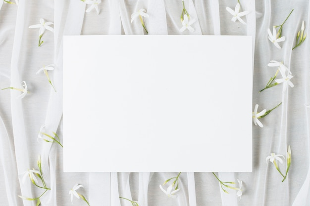 Plaque de mariage blanche entourée de fleurs de jasminum auriculatum sur un foulard