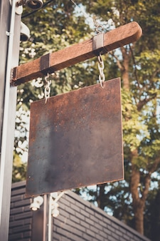 Plaque de métal rouillé blanc accroché sur la barre de bois