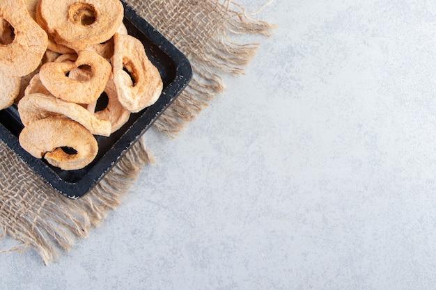 Plaque noire d'anneaux de pommes séchées saines sur pierre.