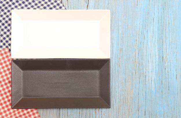 Plaque noire et blanche sur nappe sur fond de table en bois