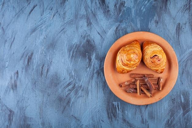 Plaque noire de deux pâtisseries fraîches sur fond bleu.