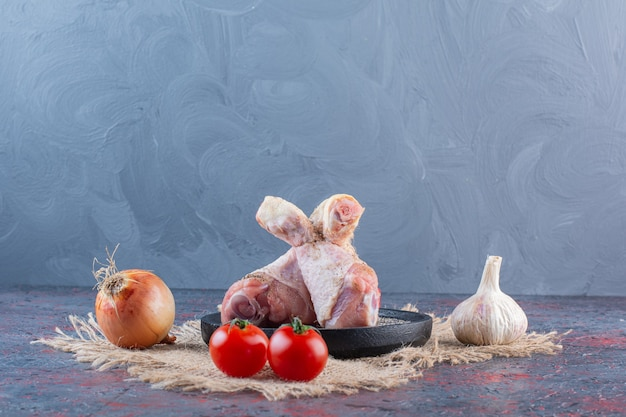 Plaque noire de morceaux de poulet cru avec des légumes sur une surface en marbre.