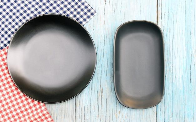 Plaque noire sur nappe sur fond de table en bois