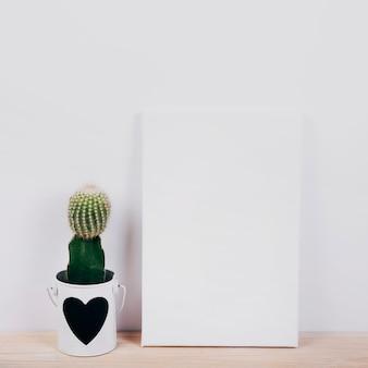 Plaque noire avec une plante succulente à cœur en forme de pot