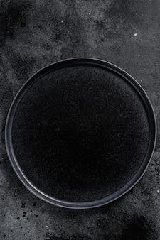 Plaque noire ronde sur fond noir texturé