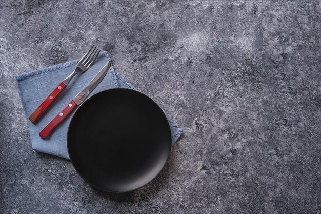 Plaque noire sur une serviette bleue sur une table en bois, vue de dessus, place pour un menu ou une recette.