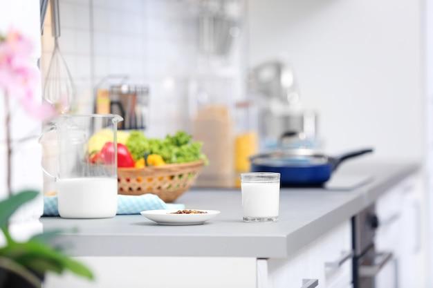 Plaque avec de la nourriture sèche et du lait préparé pour chat sur le comptoir de la cuisine