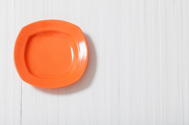 Plaque orange sur fond en bois blanc