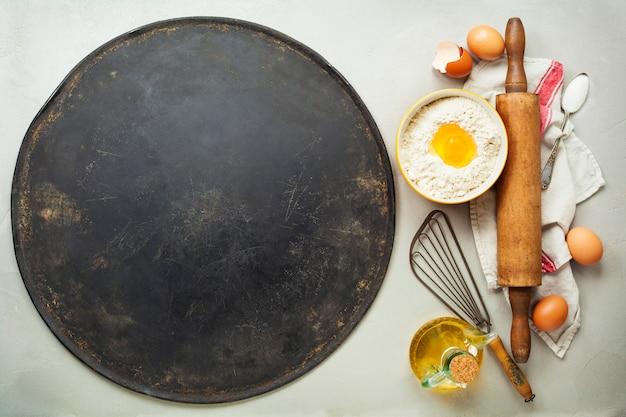 Plaque à pâtisserie et ingrédients pour pizza