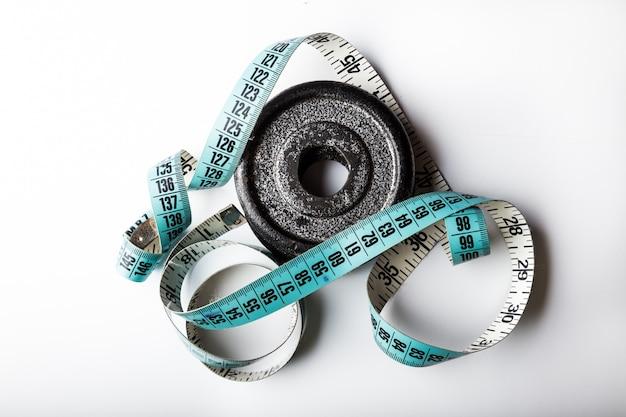 Plaque de poids avec ruban à mesurer isolé sur fond blanc