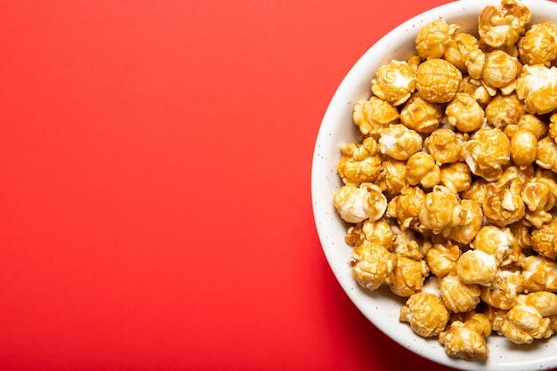 Plaque avec pop-corn au caramel sur fond rouge, vue de dessus. place pour le texte