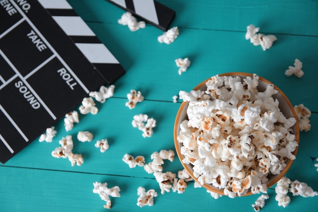 Une plaque de pop-corn sur un fond en bois bleu, vue de dessus, à côté d'un numérateur à clapet pour les films