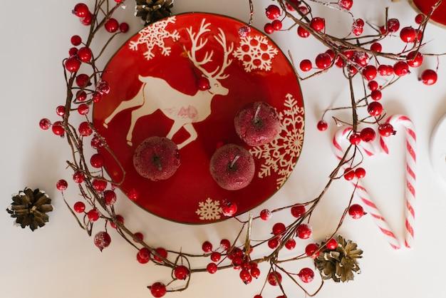 Une plaque rouge avec un motif de noël est sur la table, sur laquelle se trouvent de petites pommes rouges, à côté d'une branche aux fruits rouges. appartement de noël