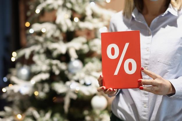 Plaque rouge avec pourcentage dans les mains des femmes du vendeur sur fond de noël arbre du nouvel an