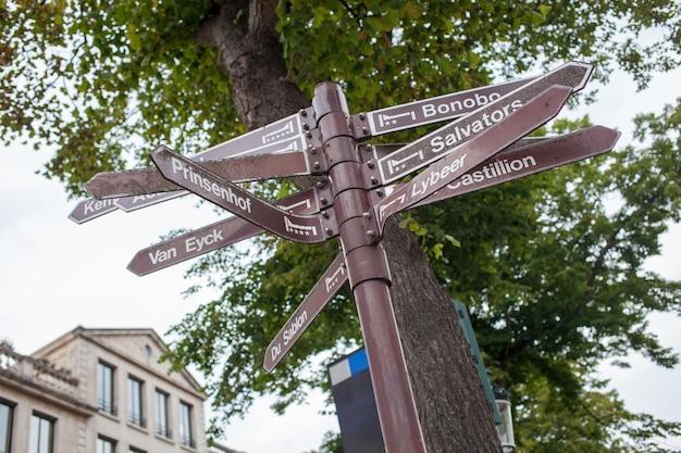 Plaque de rue avec des indications vers plusieurs monuments célèbres de bruges