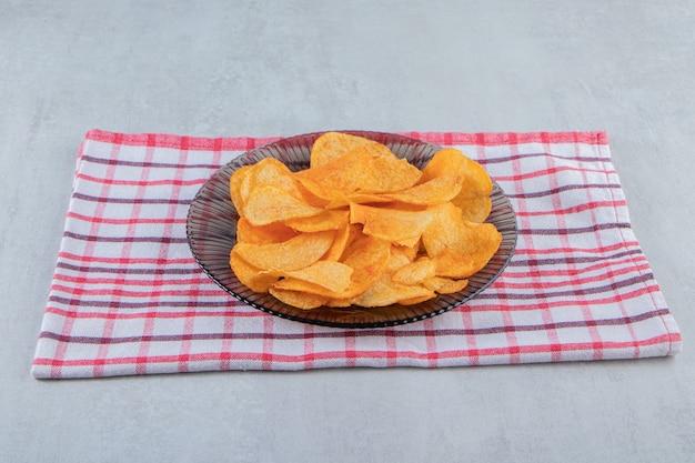Plaque de verre de chips épicées posées sur pierre.