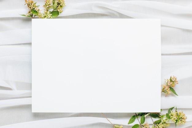 Plaque vierge blanche avec des fleurs sur le foulard