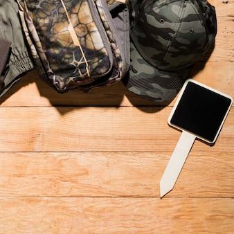 Plaque vierge avec capuchon et accessoires personnels sur une planche en bois