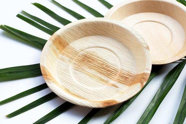 Plaques de feuilles de palmier de bétel sur fond blanc.