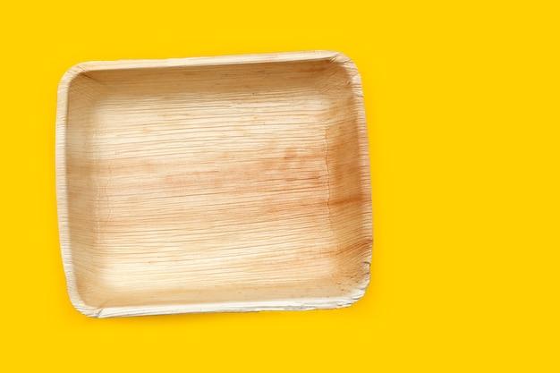 Plaques de feuilles de palmier de bétel sur fond jaune.