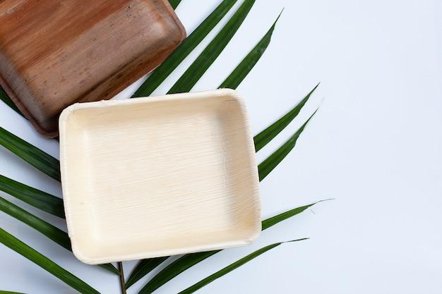 Plaques de feuilles de palmier bétel sur surface blanche