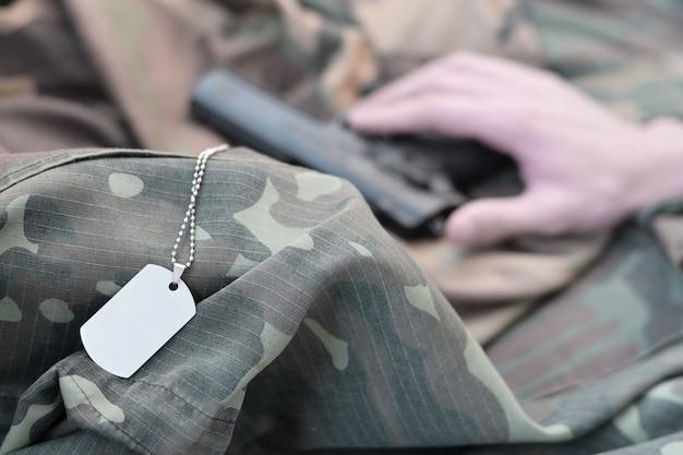 Les plaques d'identité se trouvent avec la main d'un homme dépressif qui se suicide avec une arme à feu. concept de vétéran qui ne supporte plus la douleur décide de se suicider.
