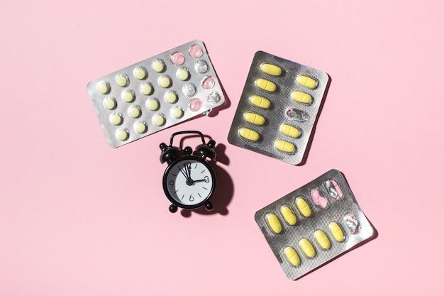 Plaques avec pilules de jaune et horloges sur fond rose, ombres dures. santé.