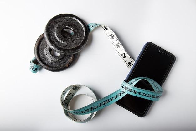 Plaques de poids et smartphone avec ruban à mesurer isoler en fond blanc