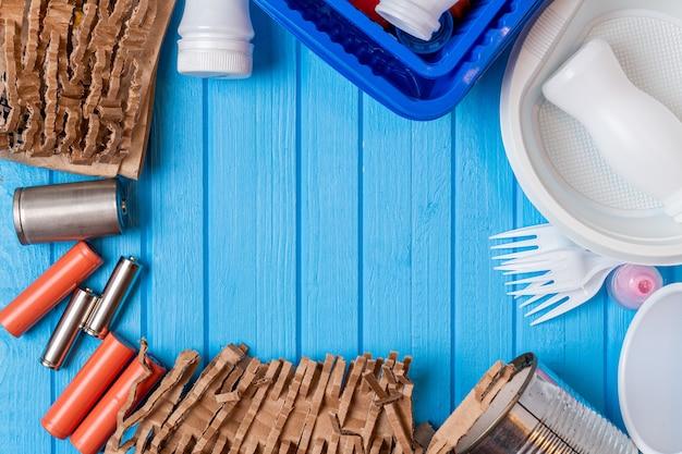 Plastique de couleur, boîtes métalliques, papier, déchets de carton sur fond bleu. concept eco avec espace copie