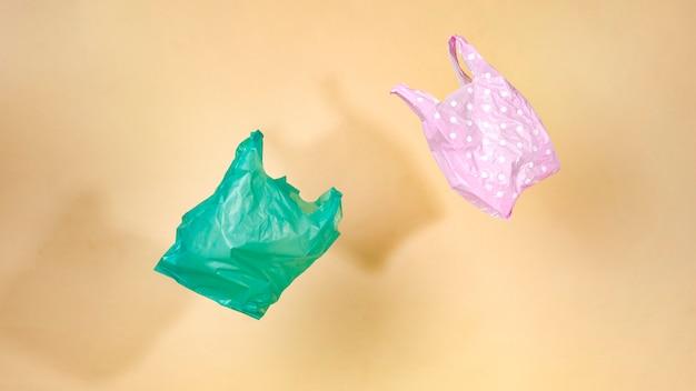 Plastiques colorés flottant avec un mur jaune