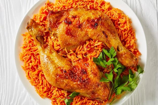 Plat d'accompagnement simple : riz à la tomate avec des quartiers de poulet rôtis cuits de riz basmati avec de la poudre de chili rouge, cannelle, cardamome, clous de girofle, persil sur une assiette blanche, vue de dessus, gros plan