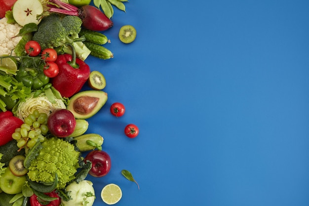 Plat d'aliments sains sur fond bleu. ensemble sain comprenant des légumes et des fruits. raisin, pomme, kiwi, poivre, citron vert, chou, courgette, pamplemousse, avocat. bonne nutrition ou menu végétarien.