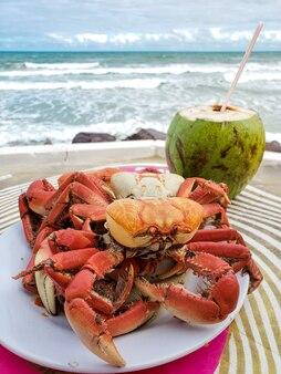 Plat apéritif aux crabes et eau de coco sur une plage face à la mer. (caueira beach, sergipe, brésil)